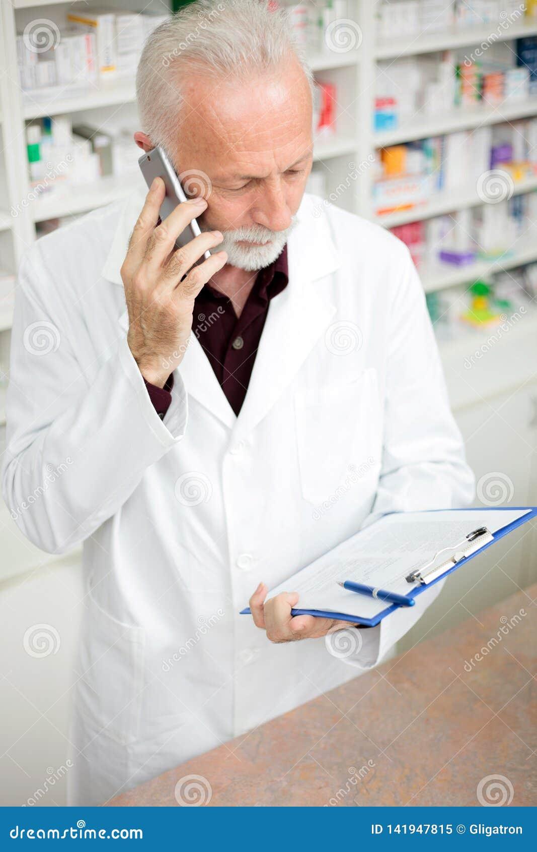 Farmacista maschio senior che parla sul telefono e che tiene una lavagna per appunti