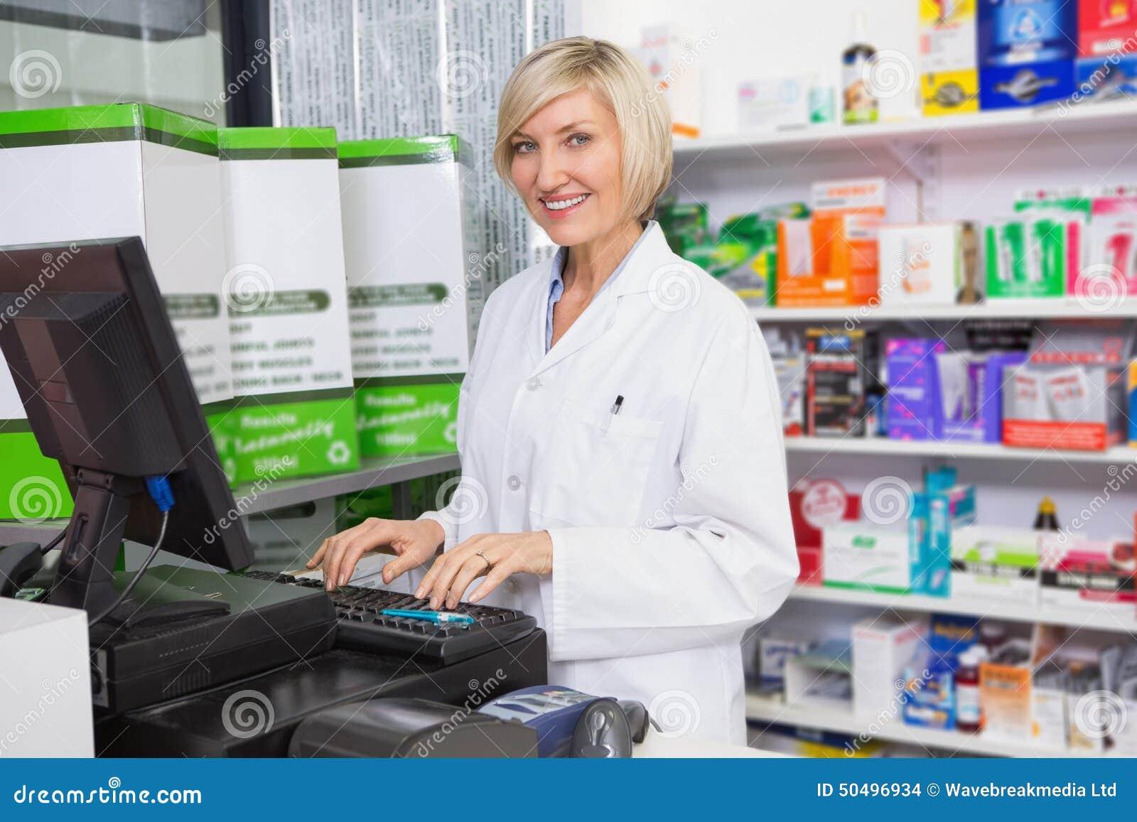 Farmacista sorridente che per mezzo del computer
