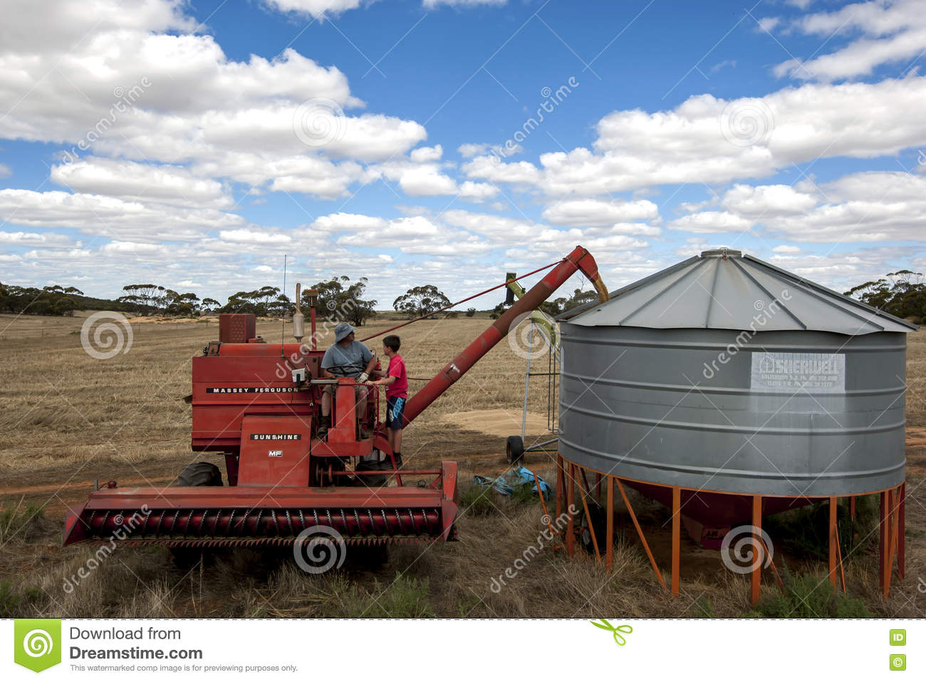 A Farmer Empties Grain From His Harvester Into A Field Silo