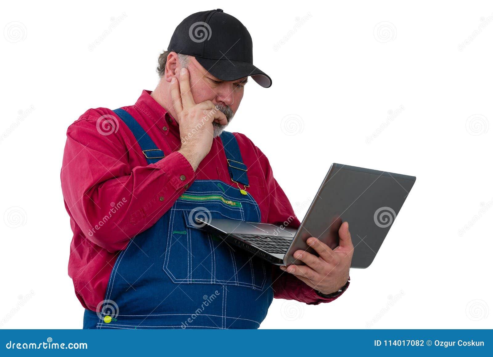 Farmer standing reading a handheld laptop computer
