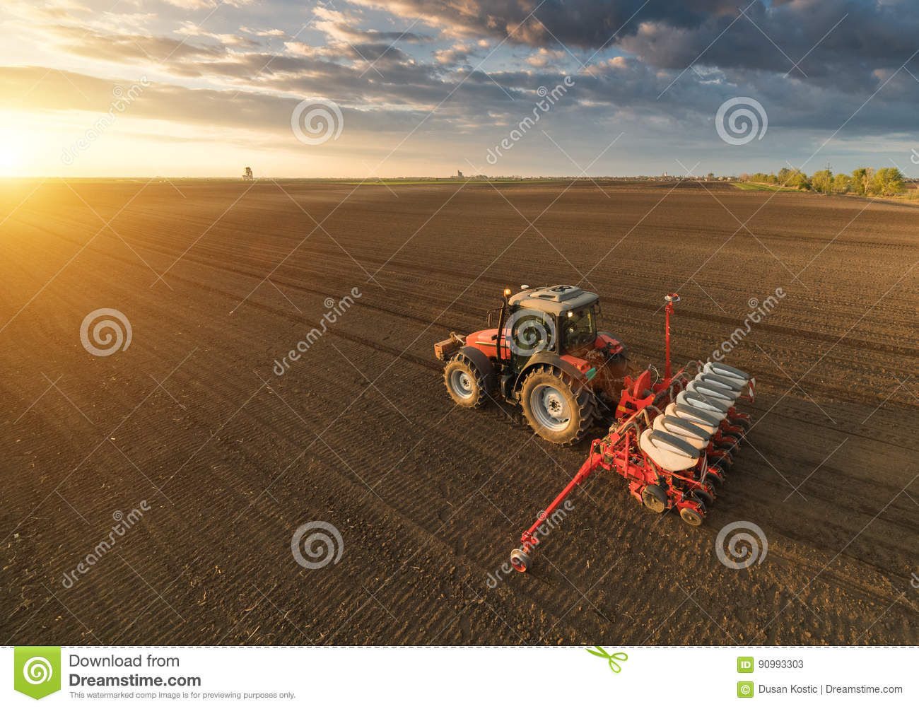 Farmer with tractor seeding - sowing crops at agricultural field