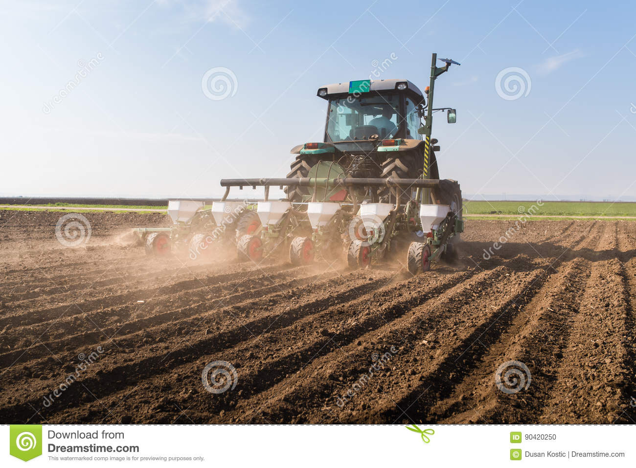 Farmer with tractor seeding - sowing soy crops at agricultural f