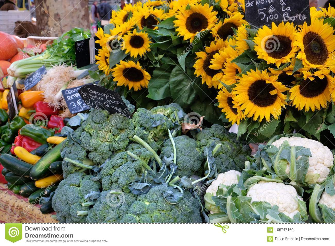 Farmers market in France with vegetables and sunflowers.