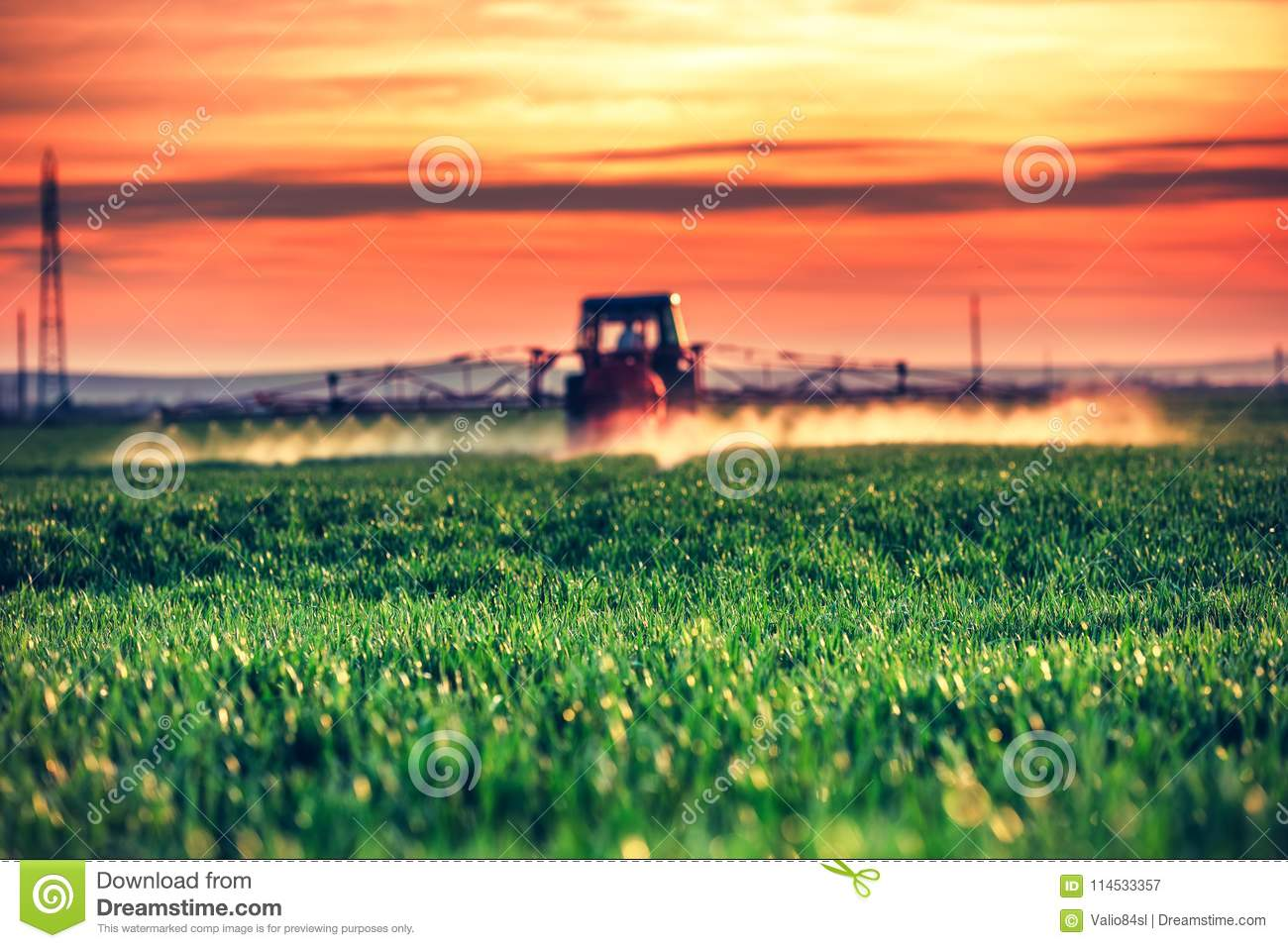 Farming tractor plowing and spraying on field by the sunset
