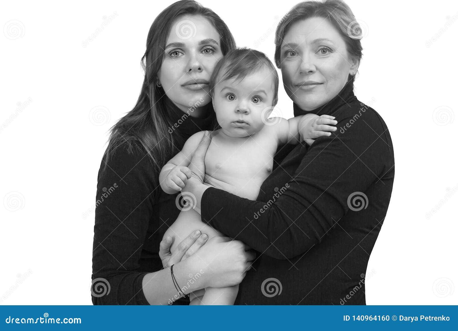 Farmor, dotter och sondotter på den vita ståenden, lyckligt familjbegrepp