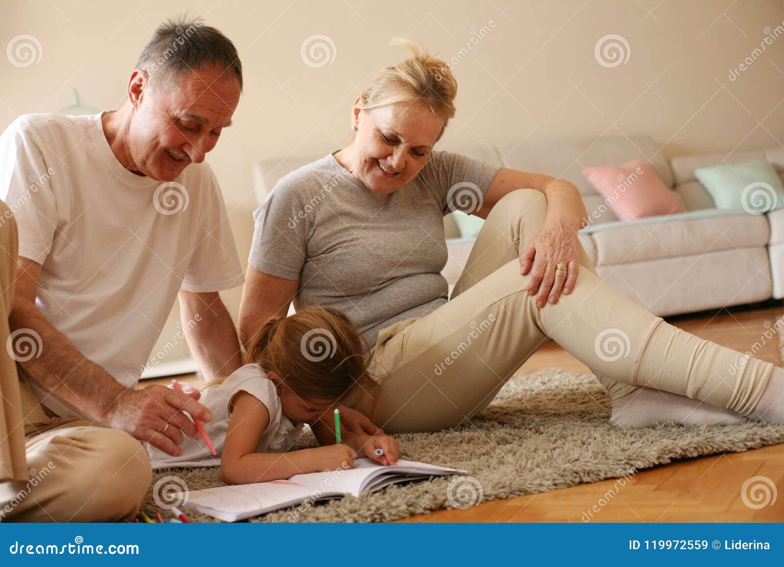 Farmor och farfar som undervisar deras sondotter till writen