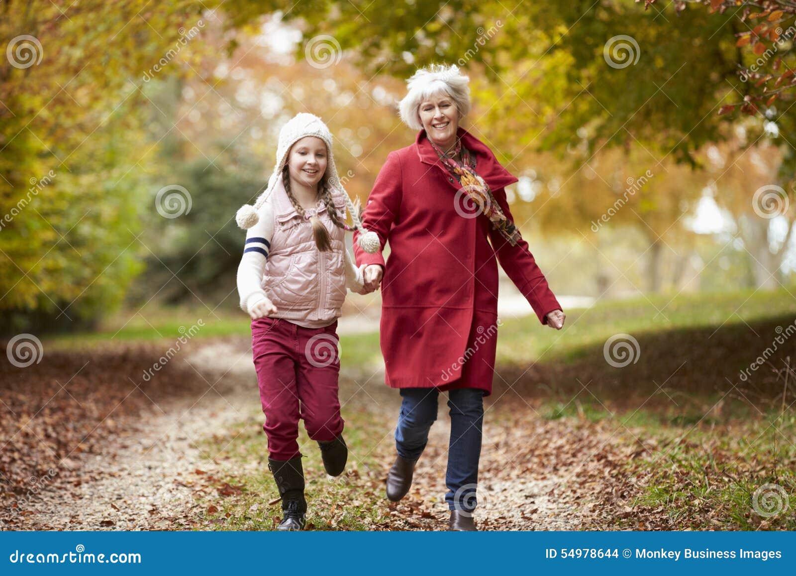 Farmorspring längs Autumn Path With Granddaughter
