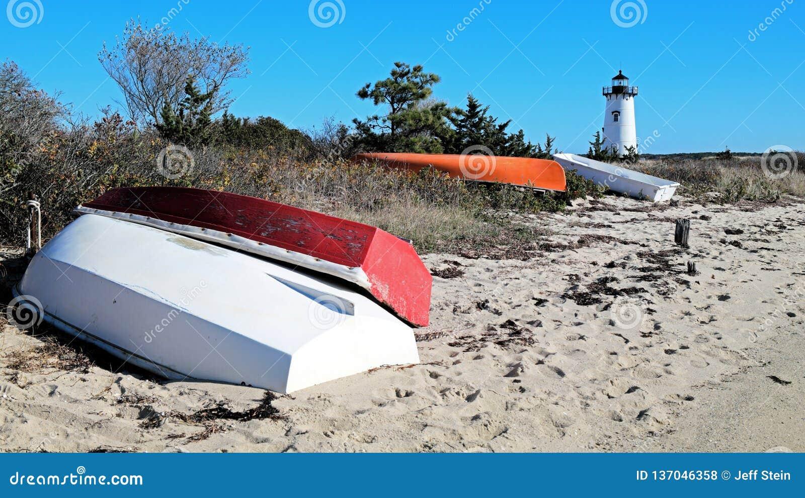 Faro de Nueva Inglaterra con los barcos de pesca coloridos en la orilla