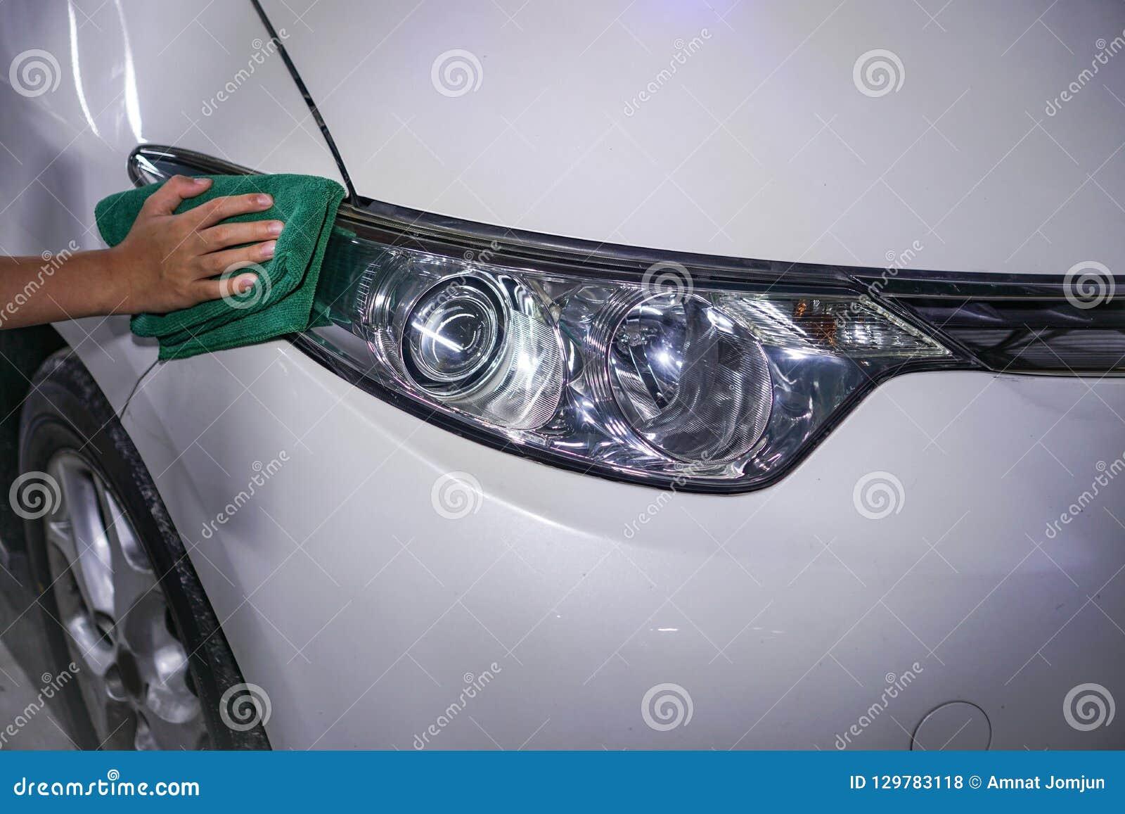 Farol de limpeza do carro da mão em um carro branco