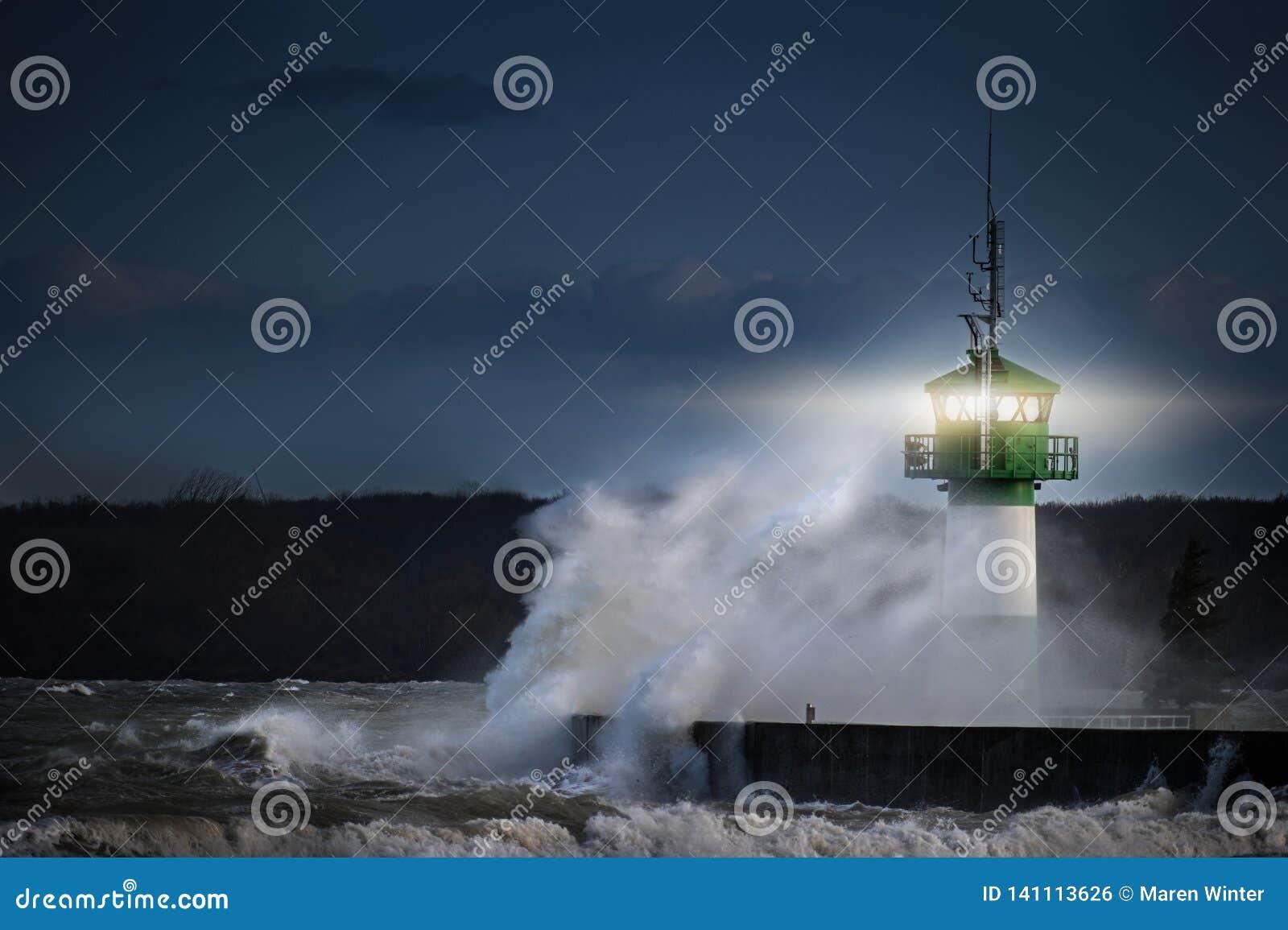 Farol durante a tempestade em espirrar o pulverizador na noite no mar Báltico, Travemuende na baía de Luebeck, espaço da cópia