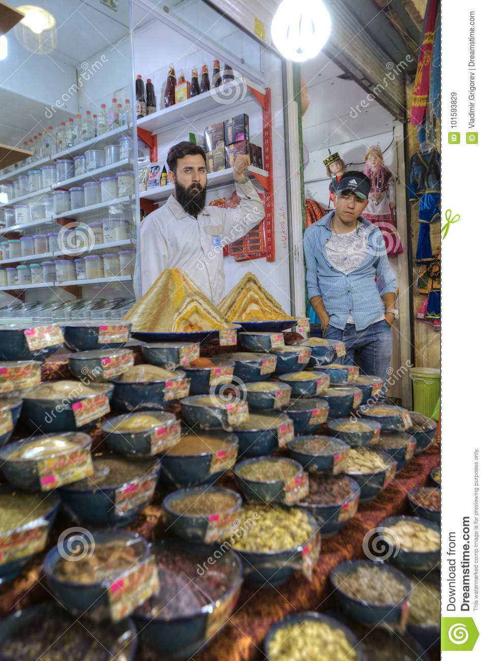 Iranian sweets traders stand near showcase of their store, Shiraz.