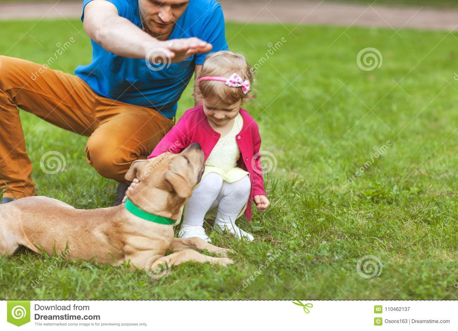 Farsa med dottern som spelar i parkera med hans hund