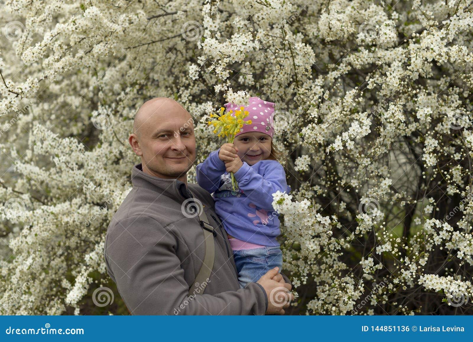 Farsa med lite dottern i hennes armar som på våren står nära ett blomma träd