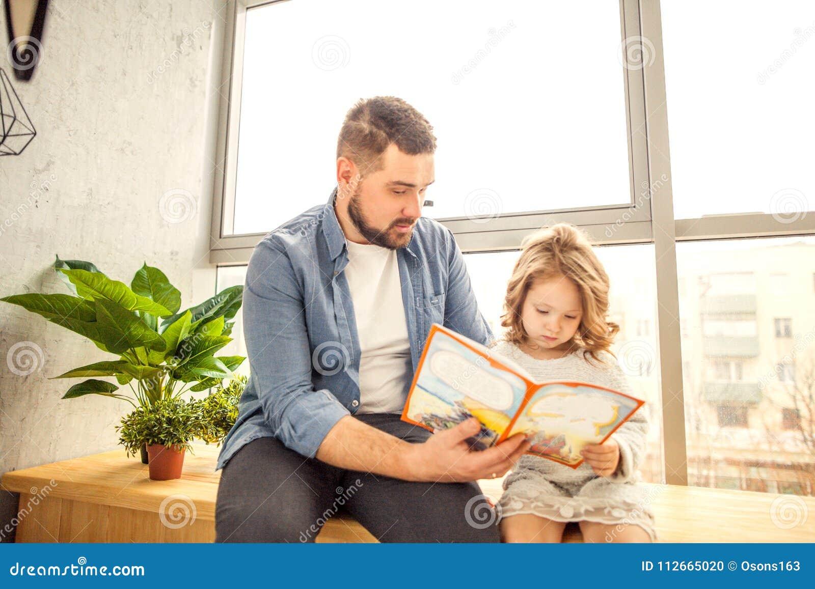 Farsa och dotter som hemma läser en bok