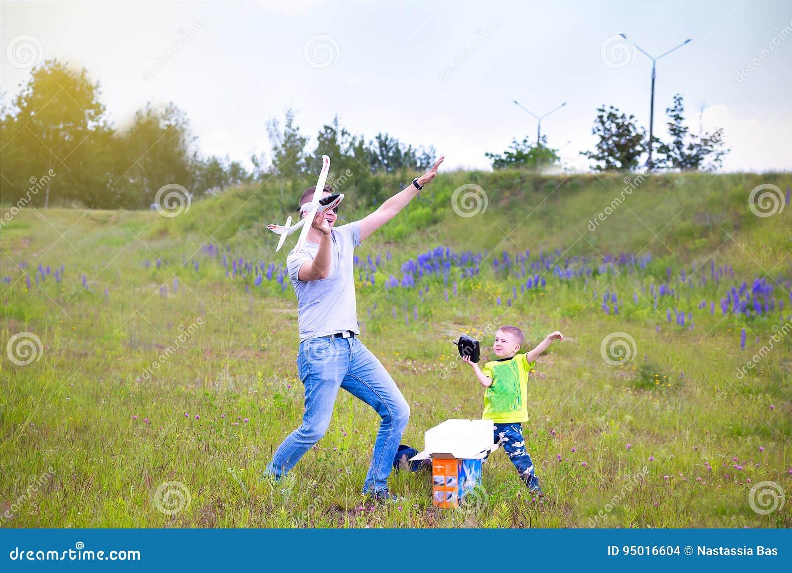 Farsa och son som spelar i flygplanet på en sommardag utomhus