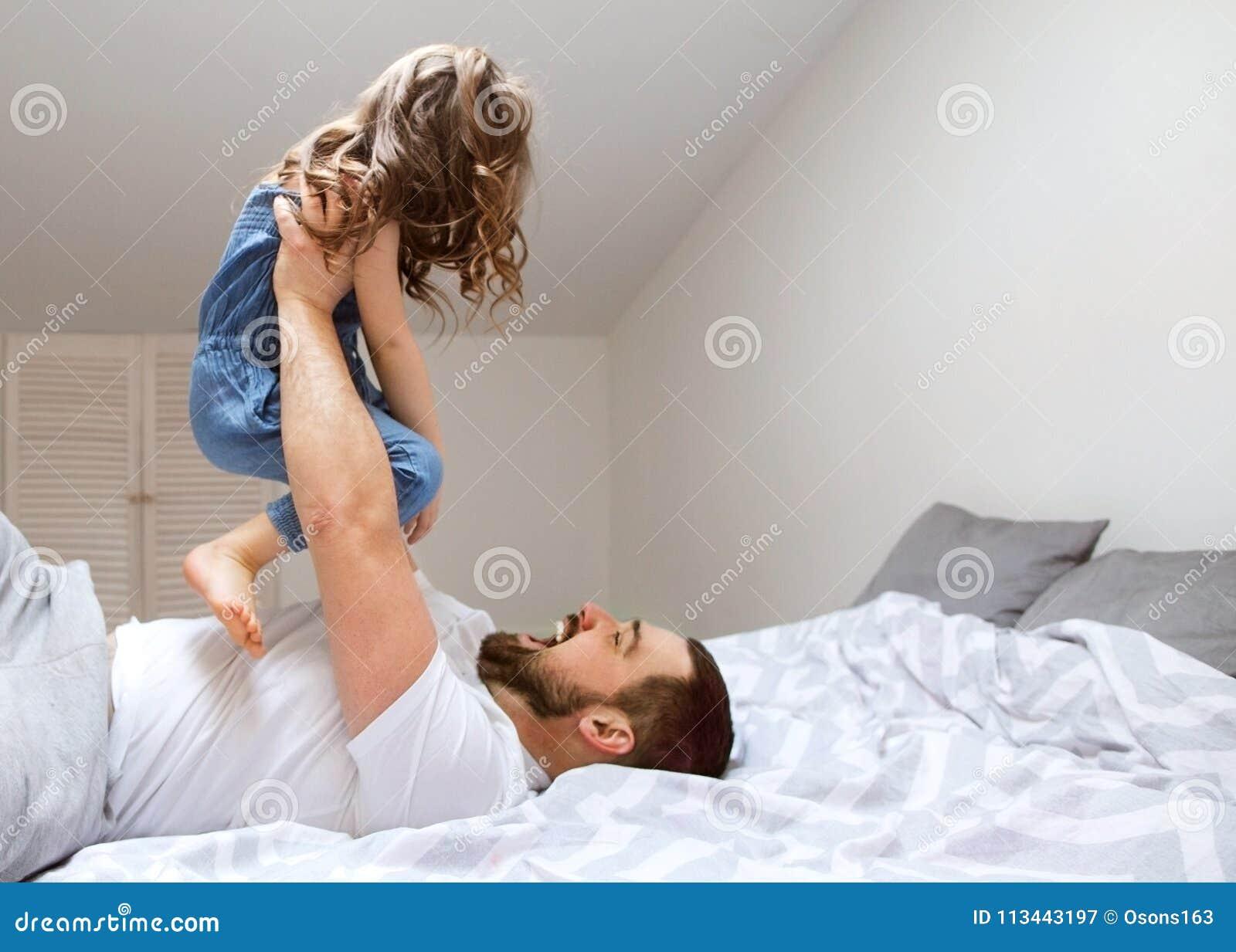 Farsan och dottern har roligt hemma på sängen dagfader s