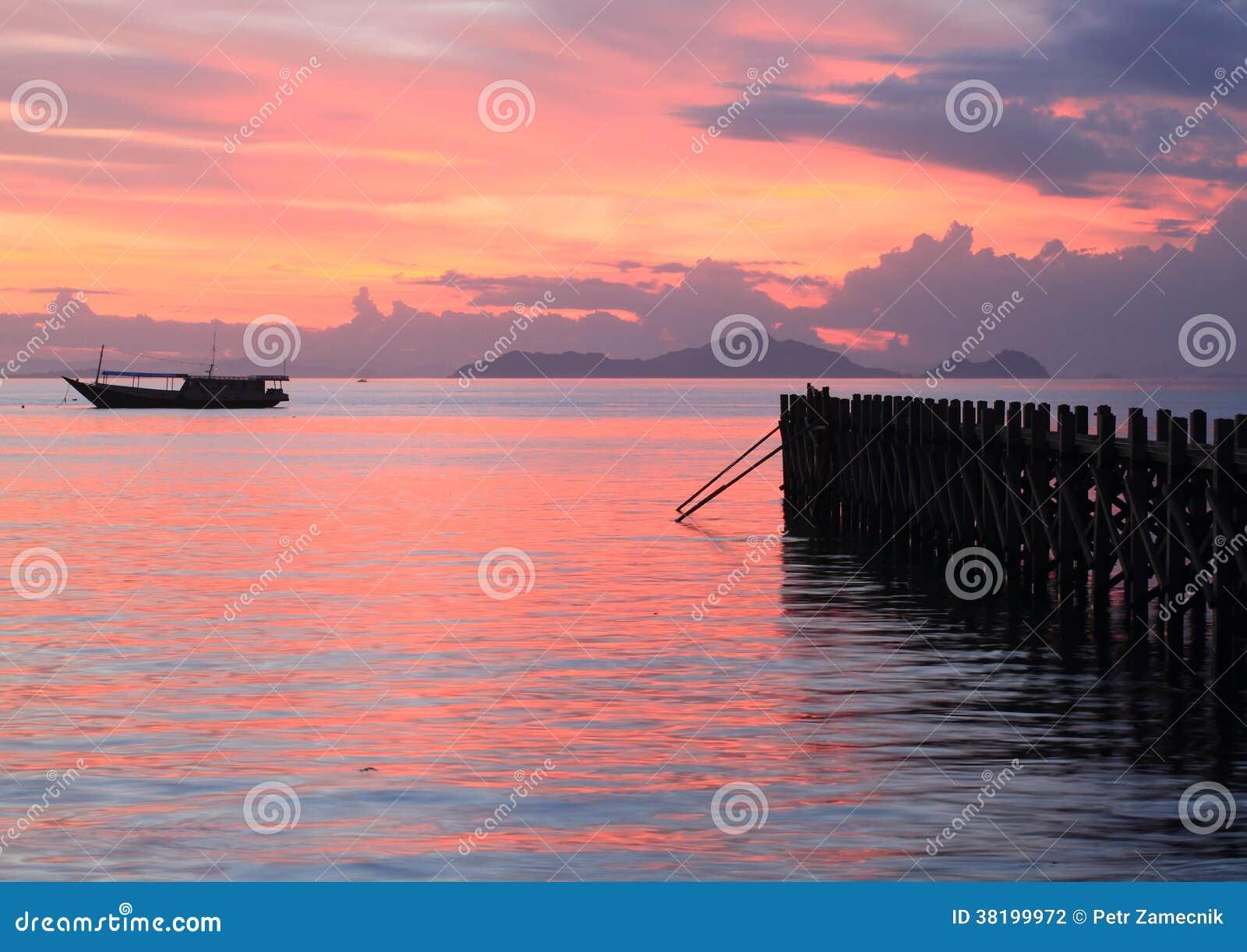 Fartyg och brygga på solnedgånghavet
