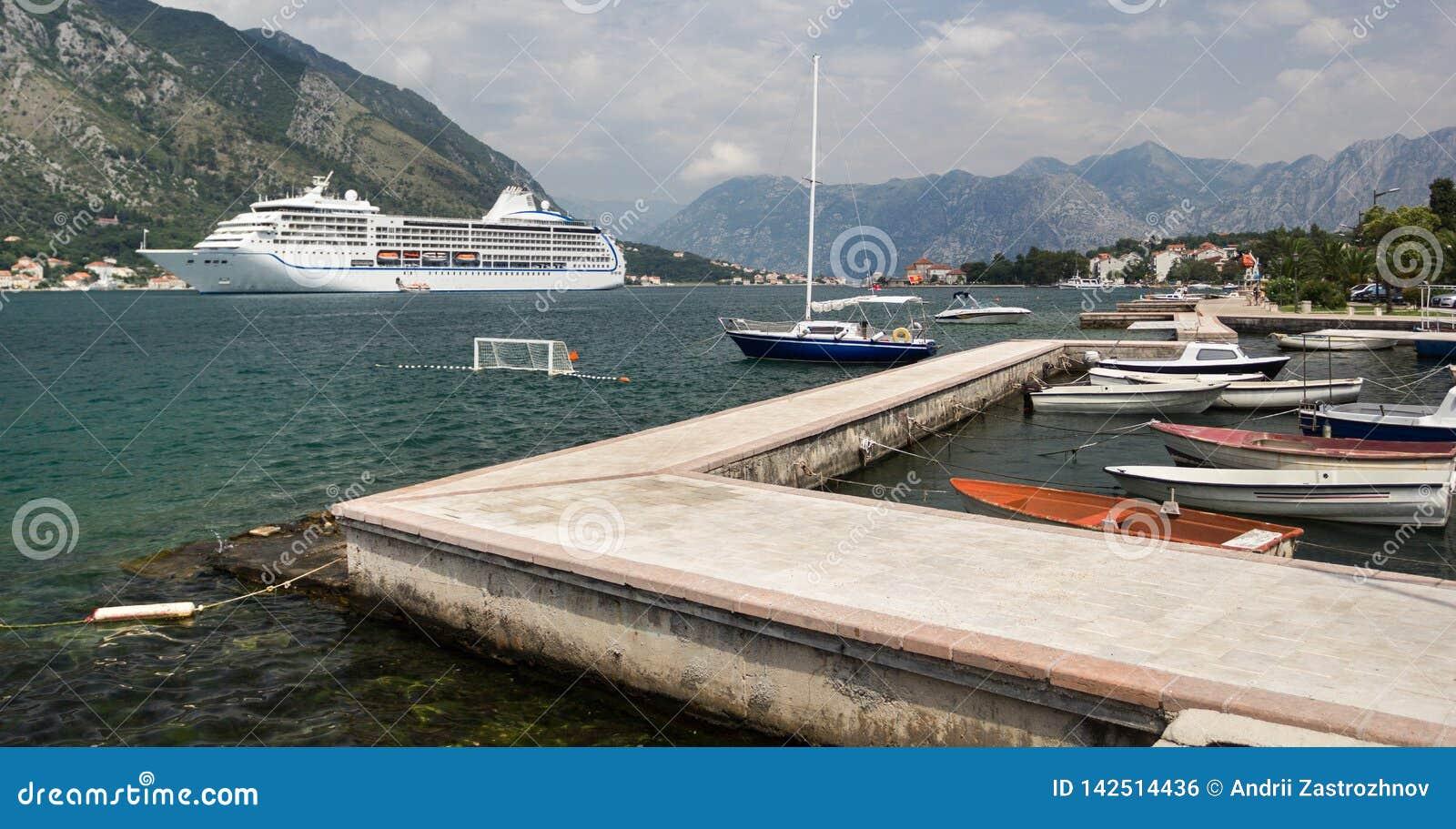 Fartyg på marina i fjärden Kryssningskepp i bakgrunden