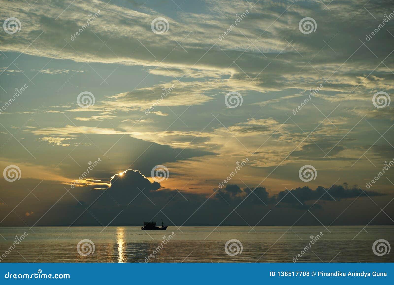 Fartyg på solnedgången och soluppgång med dramatisk himmel över havet