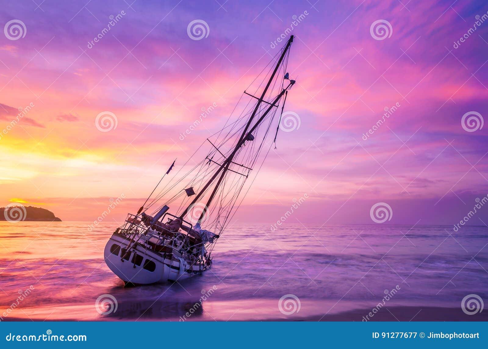 Fartyg på stranden i skymning och färgrikt av solnedgången