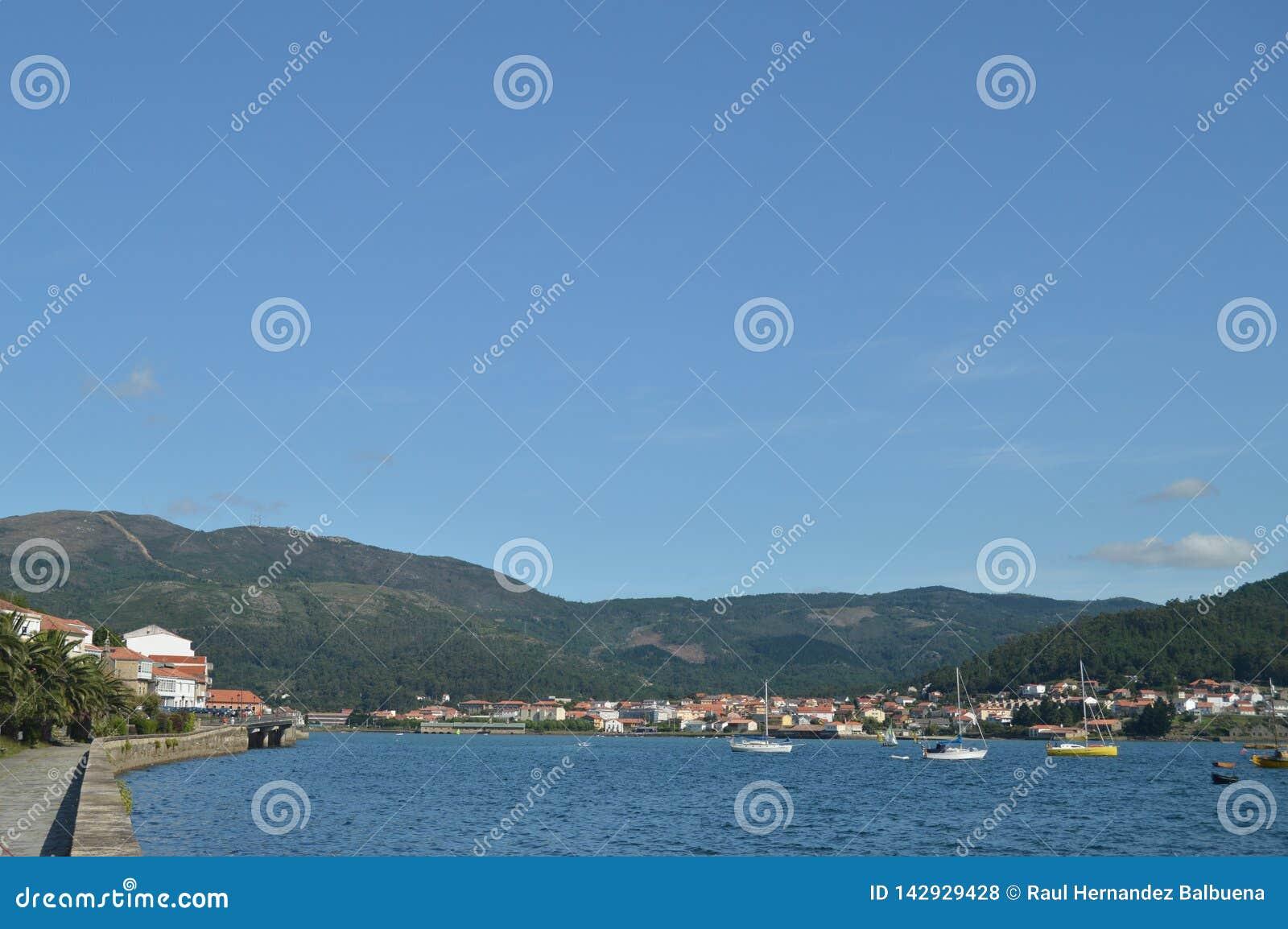 Fartyg som förtöjas tillsammans med musslaavelsdjur i breda flodmynningen av den Muros byn Natur arkitektur, historia, gatafotogr
