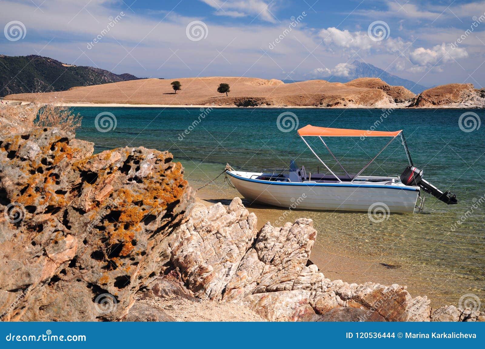 Fartyg som parkeras i lagun för blått vatten av den Ammouliani ön, Halkidiki, Grekland