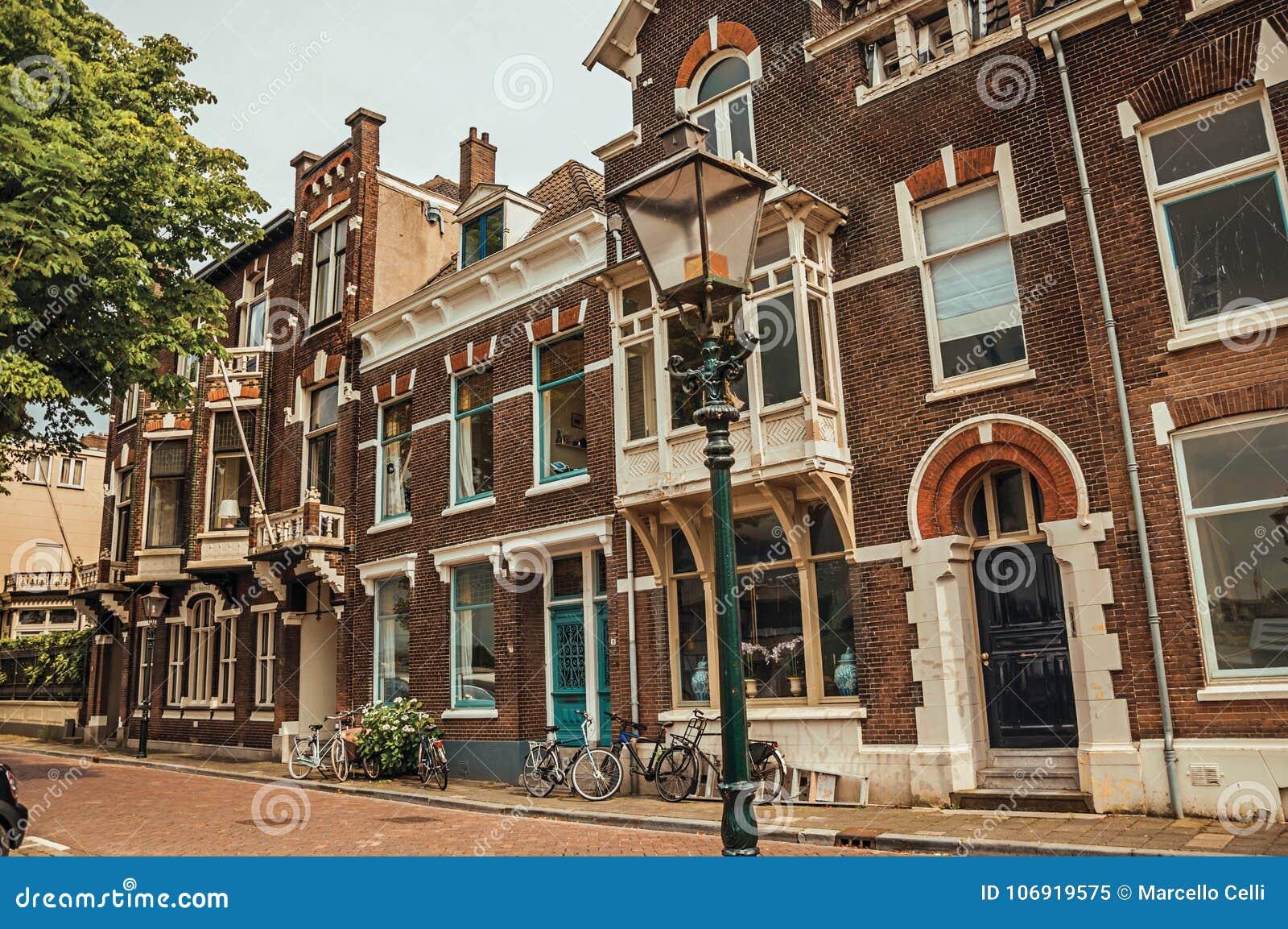 Fasada eleganccy ceglani domy i bicykle na ulicie w chmurnym dniu przy Dordrecht