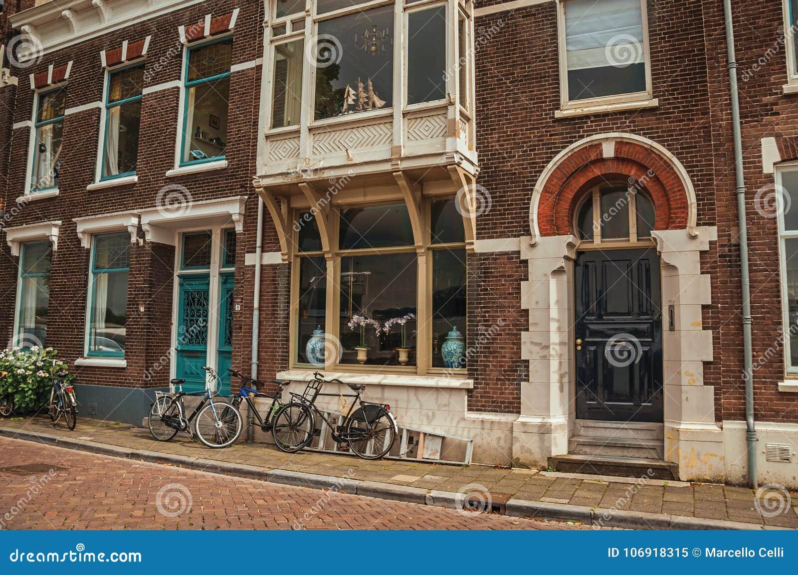 Fasada elegancki ceglany dom z drzwi w niezwykłym projekcie i bicykle na ulicie w Dordrecht
