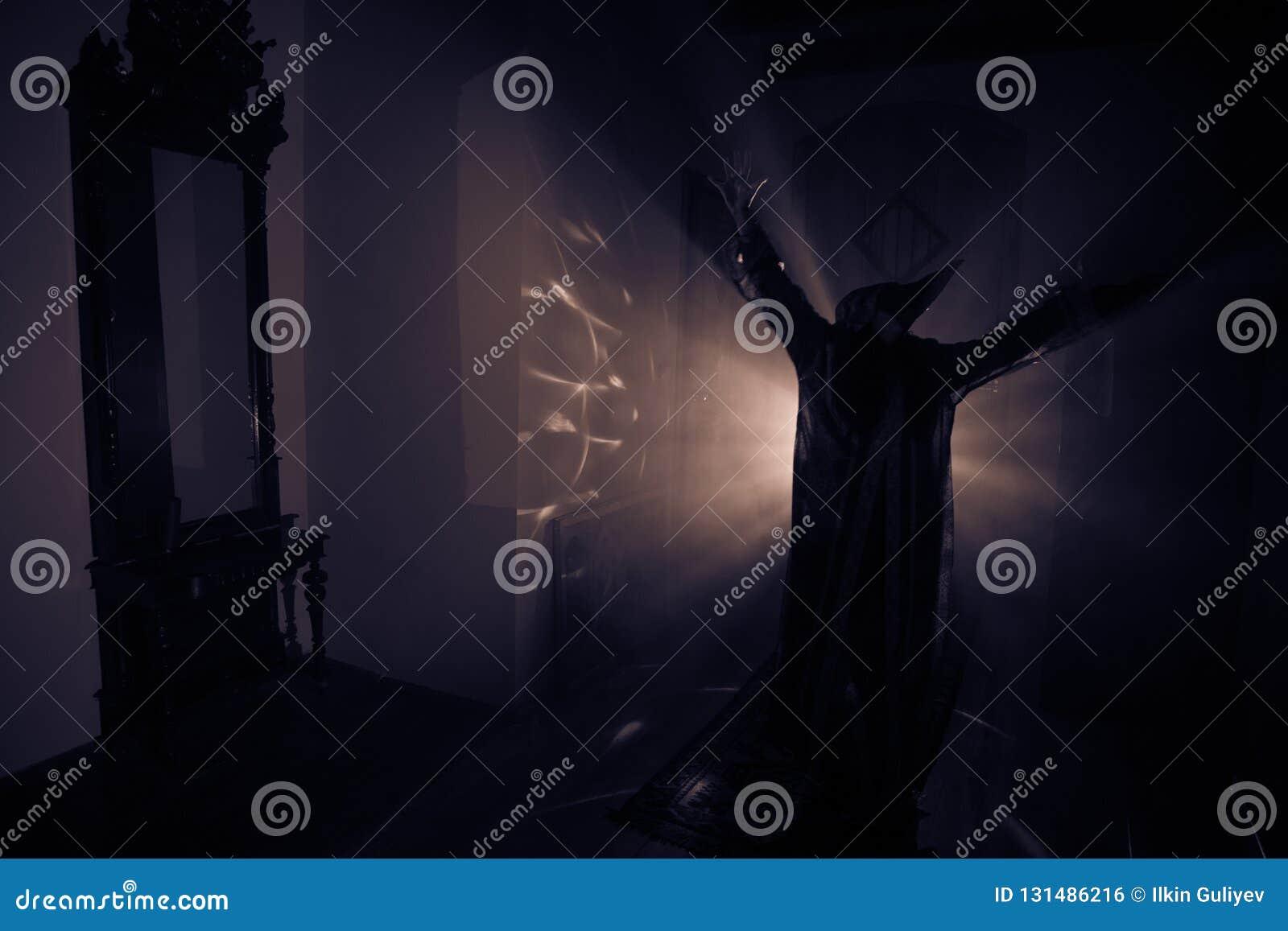 Fasakontur av spöken inom mörkt rum med spegeln Läskigt halloween begrepp Kontur av häxan inom spökat hus med