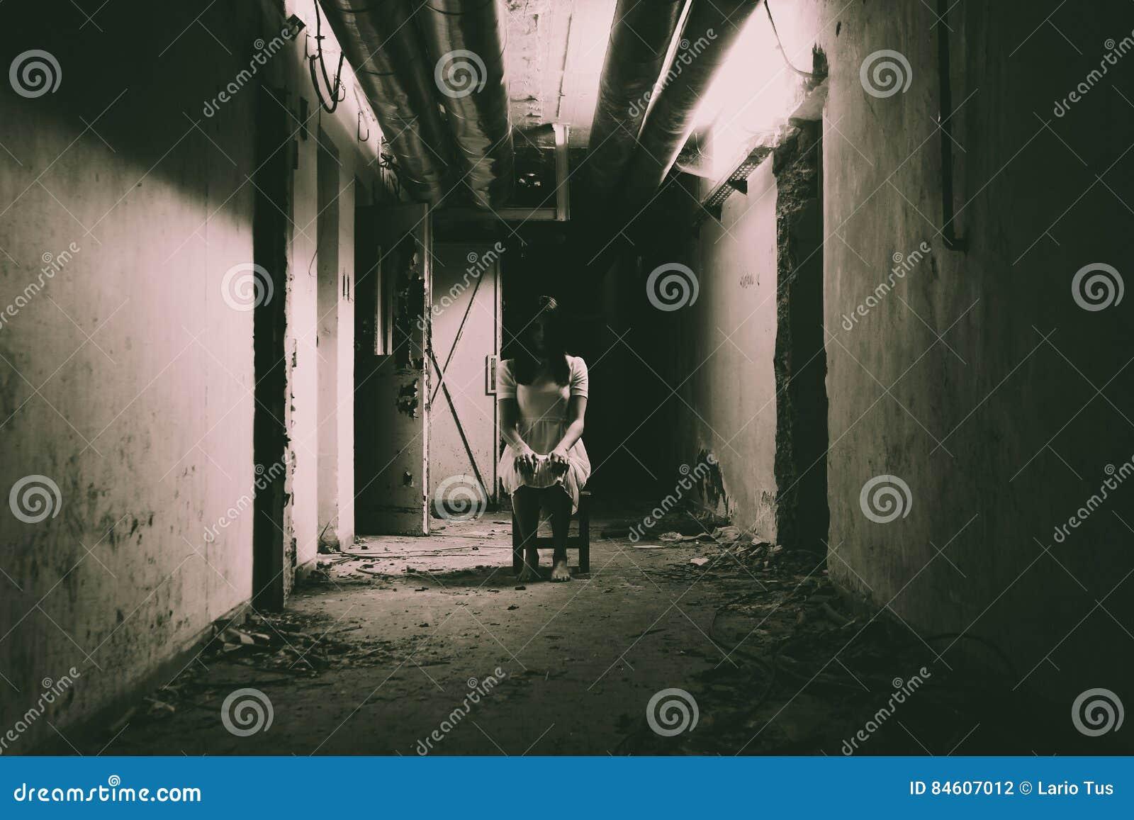 Fasaplats av en läskig kvinna i mörkt hall