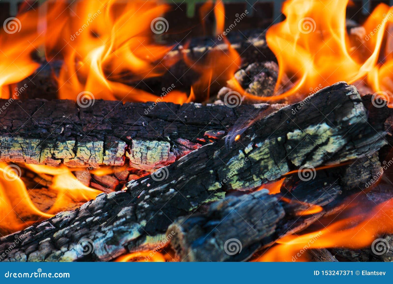 Fascinera brasan, med glödande trä- och slingra sigflammor Texturen av det brinnande trädet