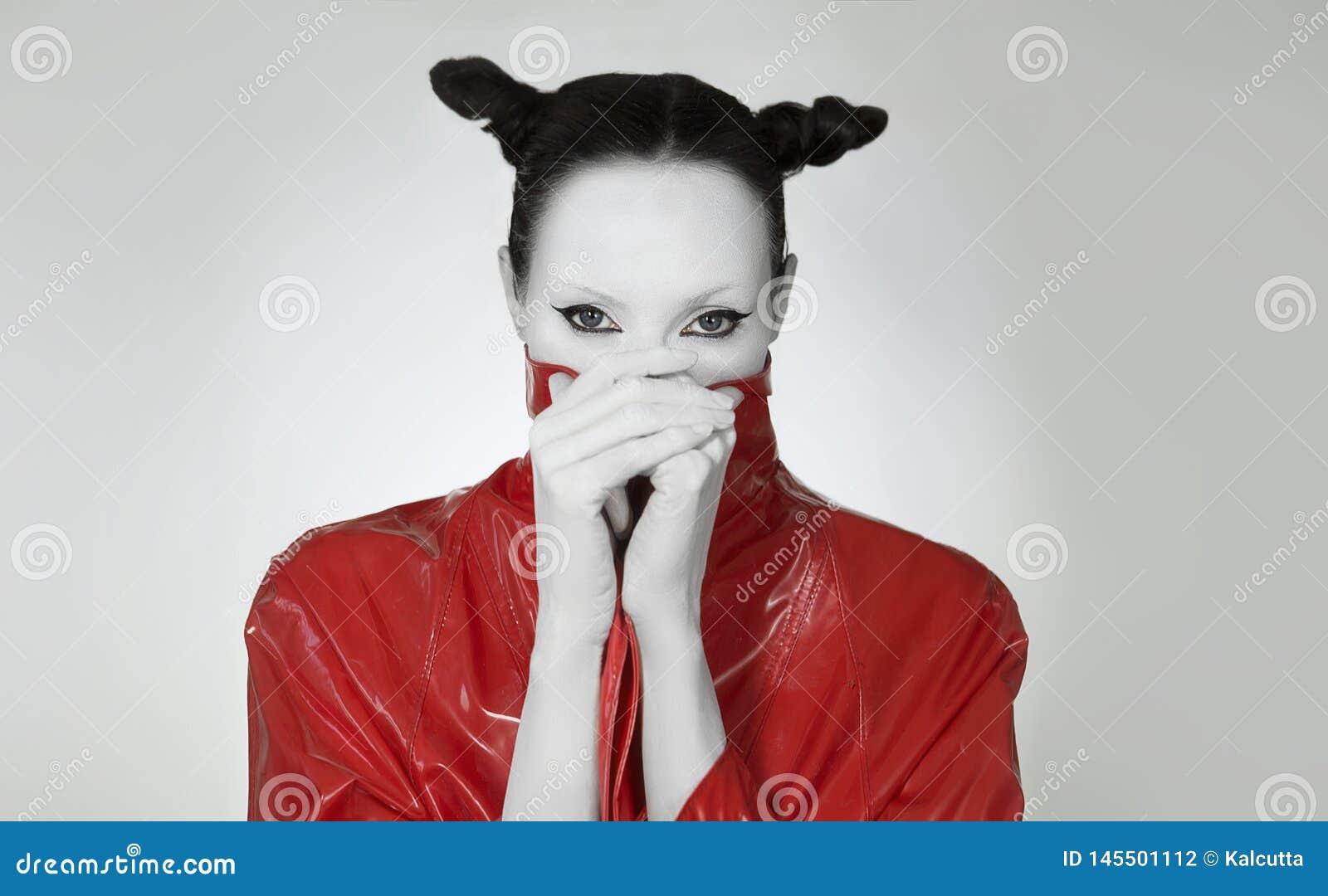 Fascino creativo Giovane donna in impermeabile lungo rosso alla moda della lacca Trucco pazzo di modo