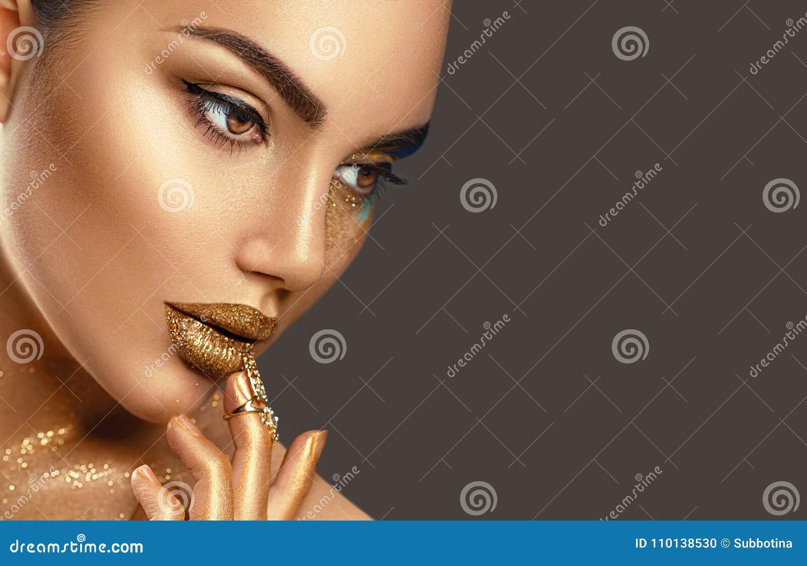 Fashion art makeup. Portrait of beauty woman with golden skin. Shiny professional makeup