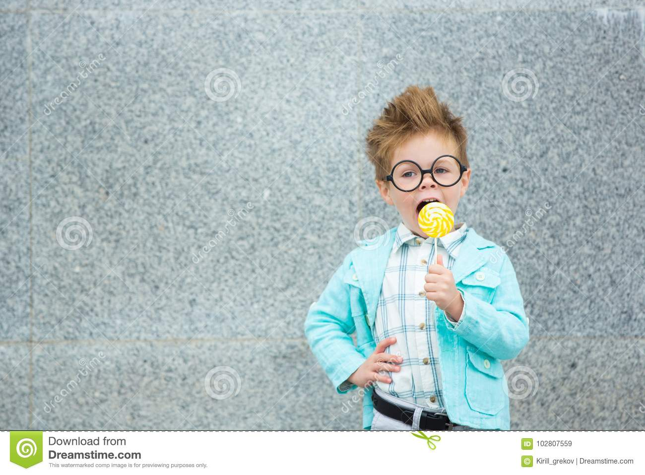 Fashion kid with lollipop near gray wall
