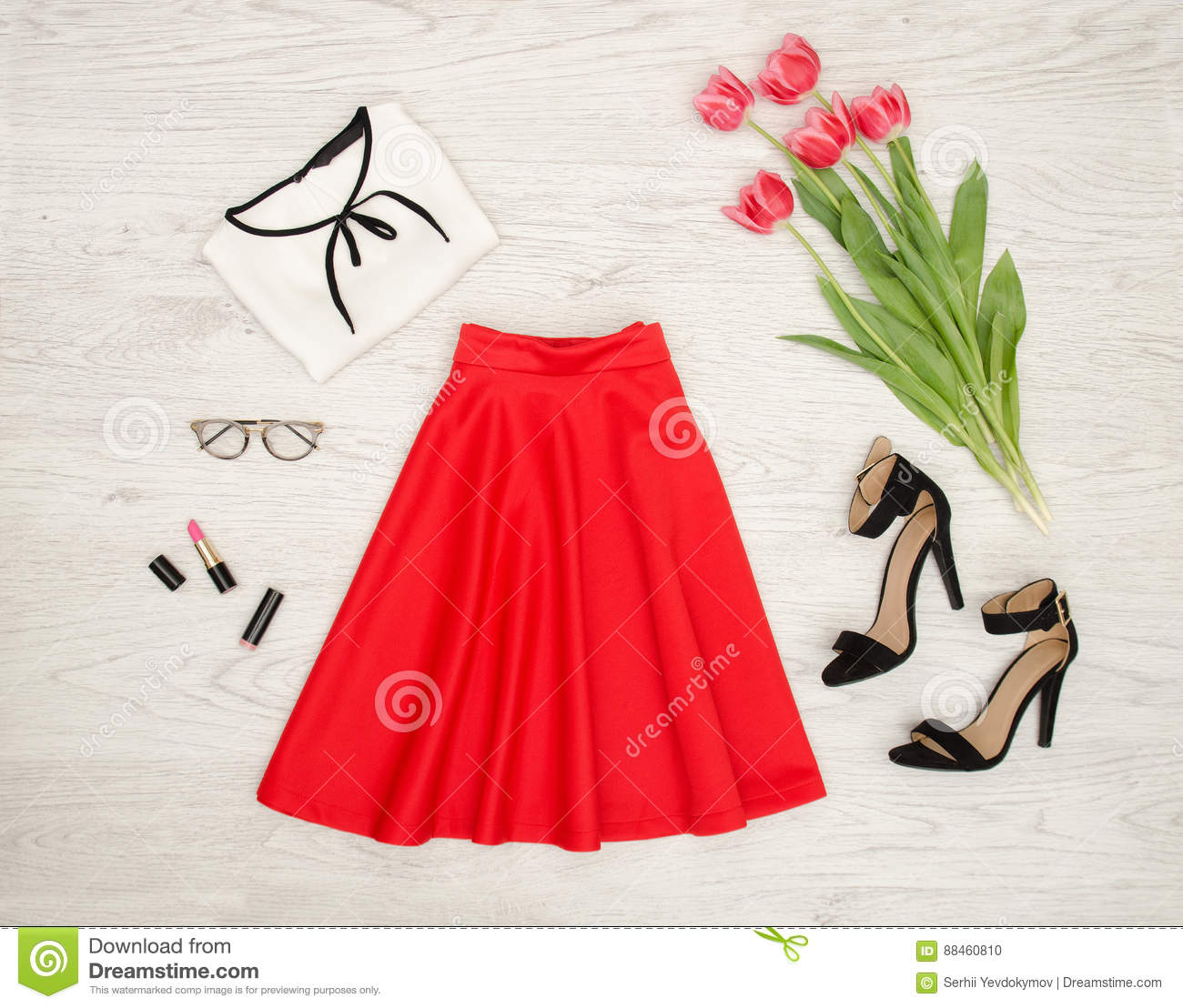 Fashion concept. Red skirt, blouse, sunglasses, lipstick, black shoes and pink tulips. Top view, light wood background