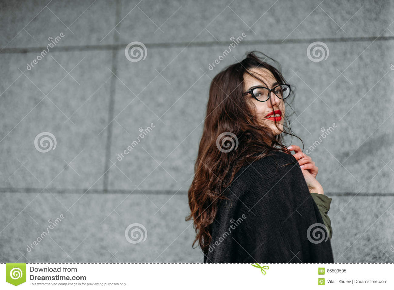 Fashion consept: beatiful young girl with long hair, glasses, red lips standing near modern wall wearing in green suit and grey je