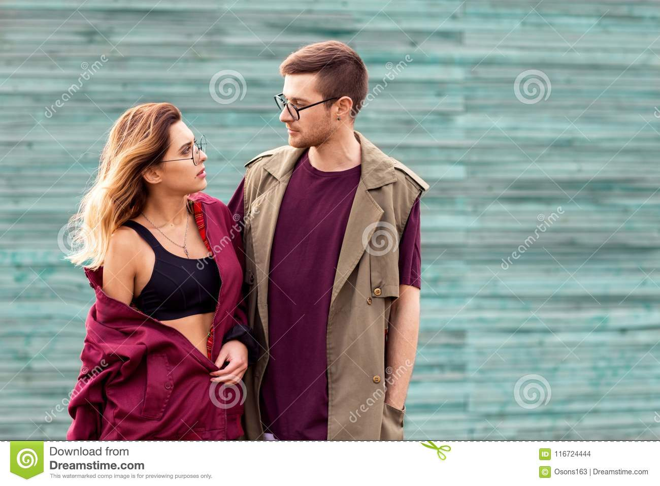 abf815da4ca Fashion Couple In Their Glasses With Burgundy Clothes Posing On ...