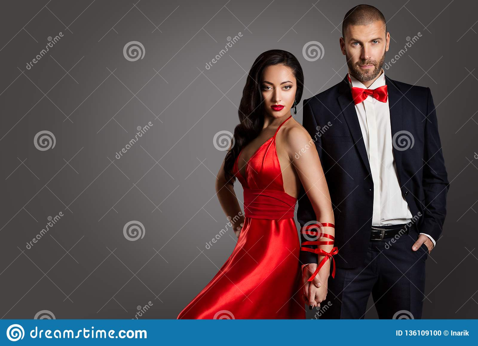 Fashion Couple, Woman and Man Arms Bounded by Ribbon, Red Dress Black Suit