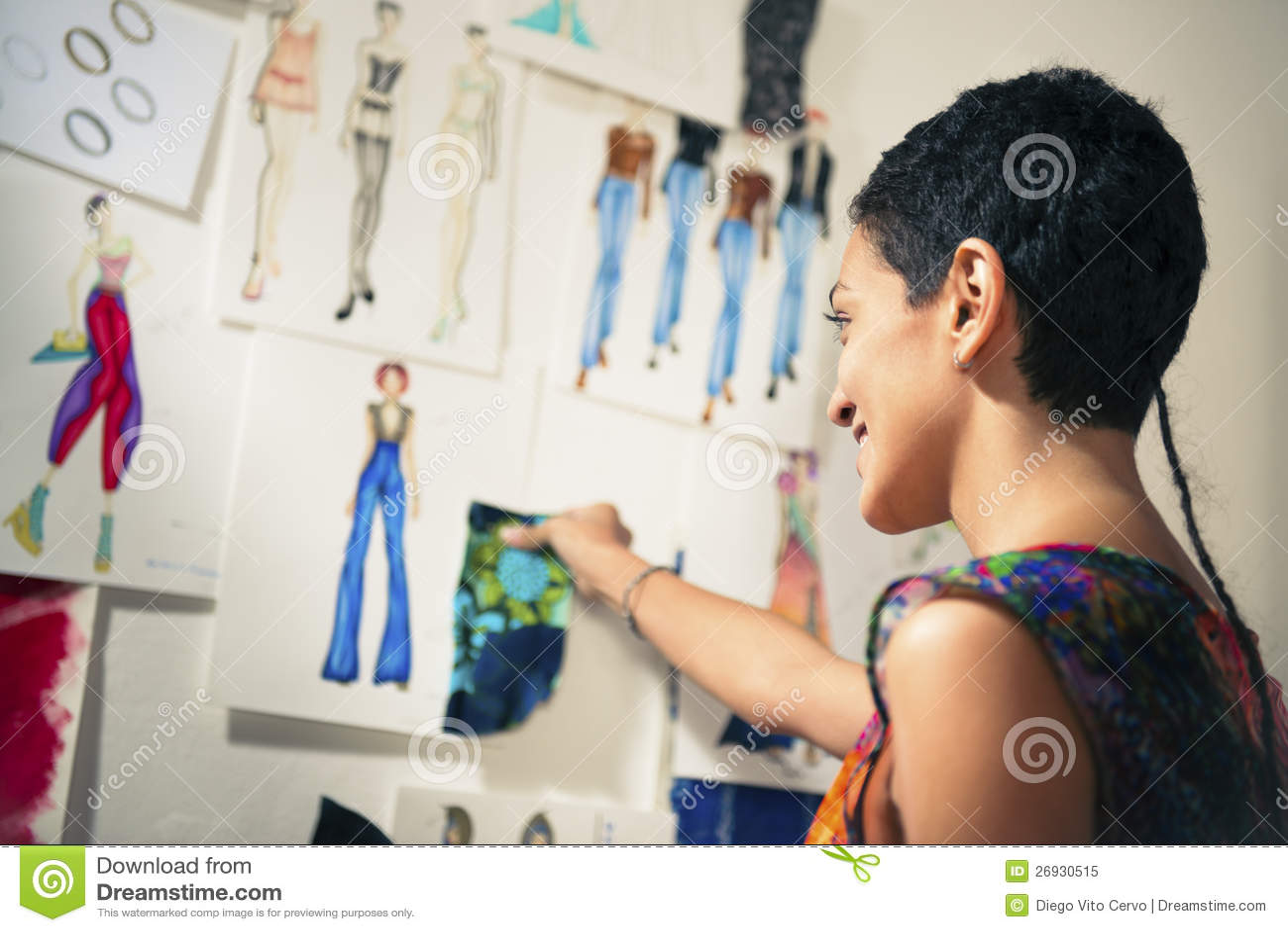 Fashion designer contemplating drawings in studio