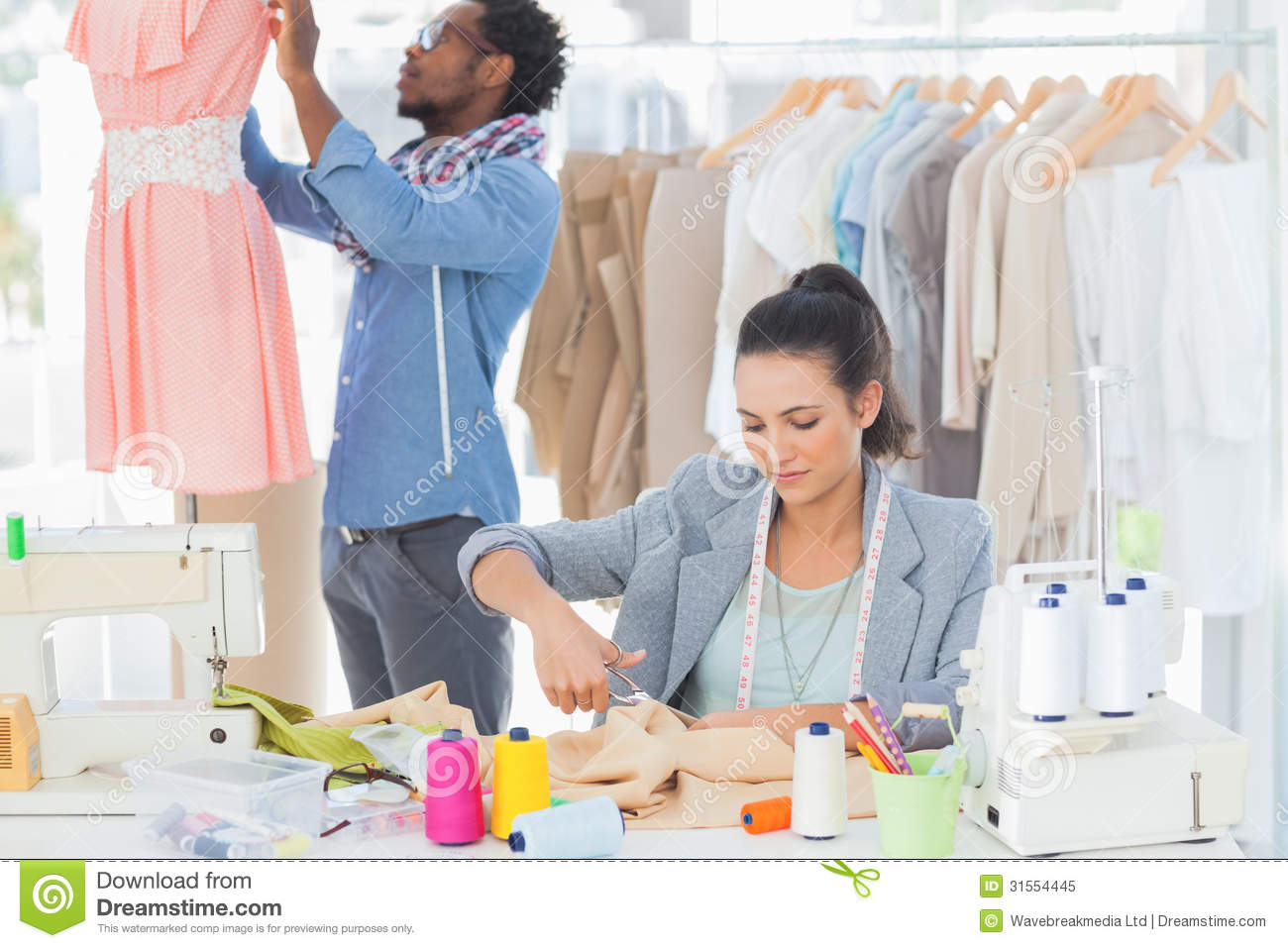Fashion Designer Cutting Textile At Desk Royalty Free