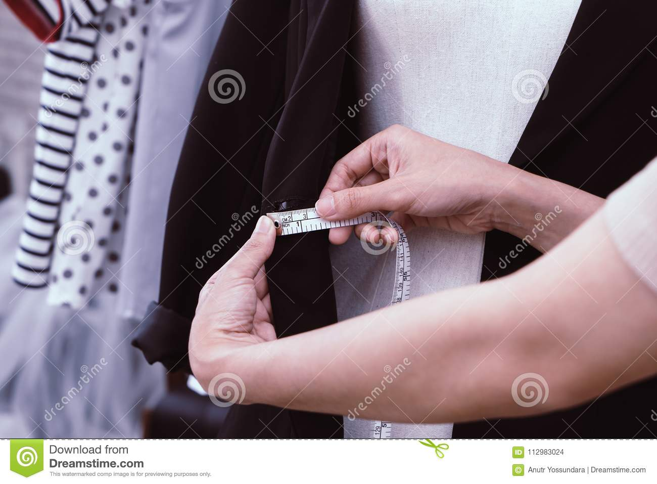 Fashion Designer hand measuring clothes with measuring tape