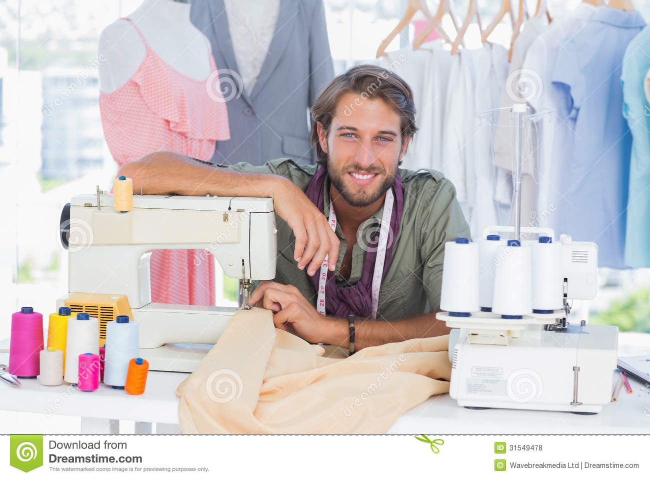fashion designer leaning on sewing machine royalty free