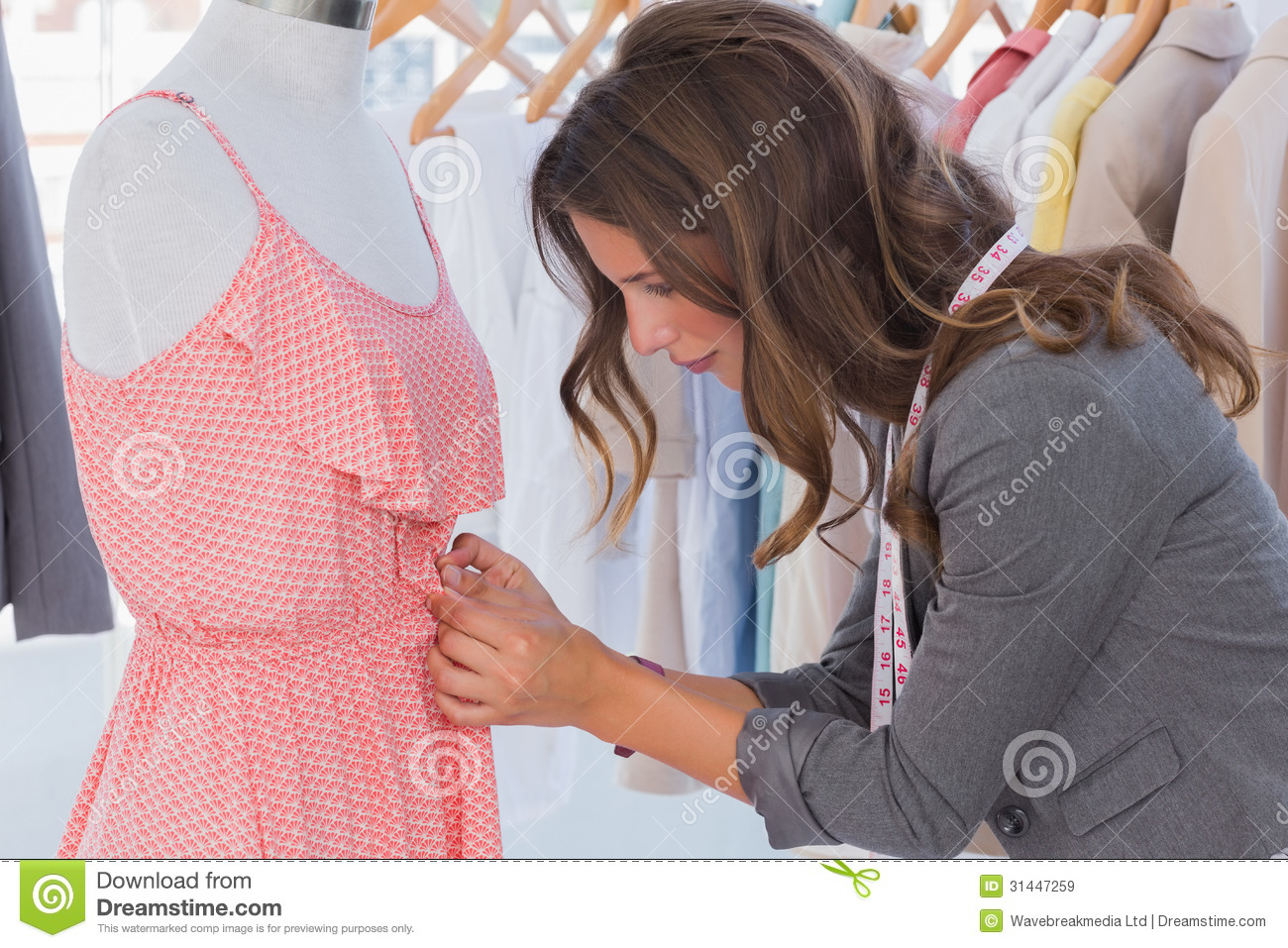 Fashion Designer Measuring Dress On A Mannequin Stock
