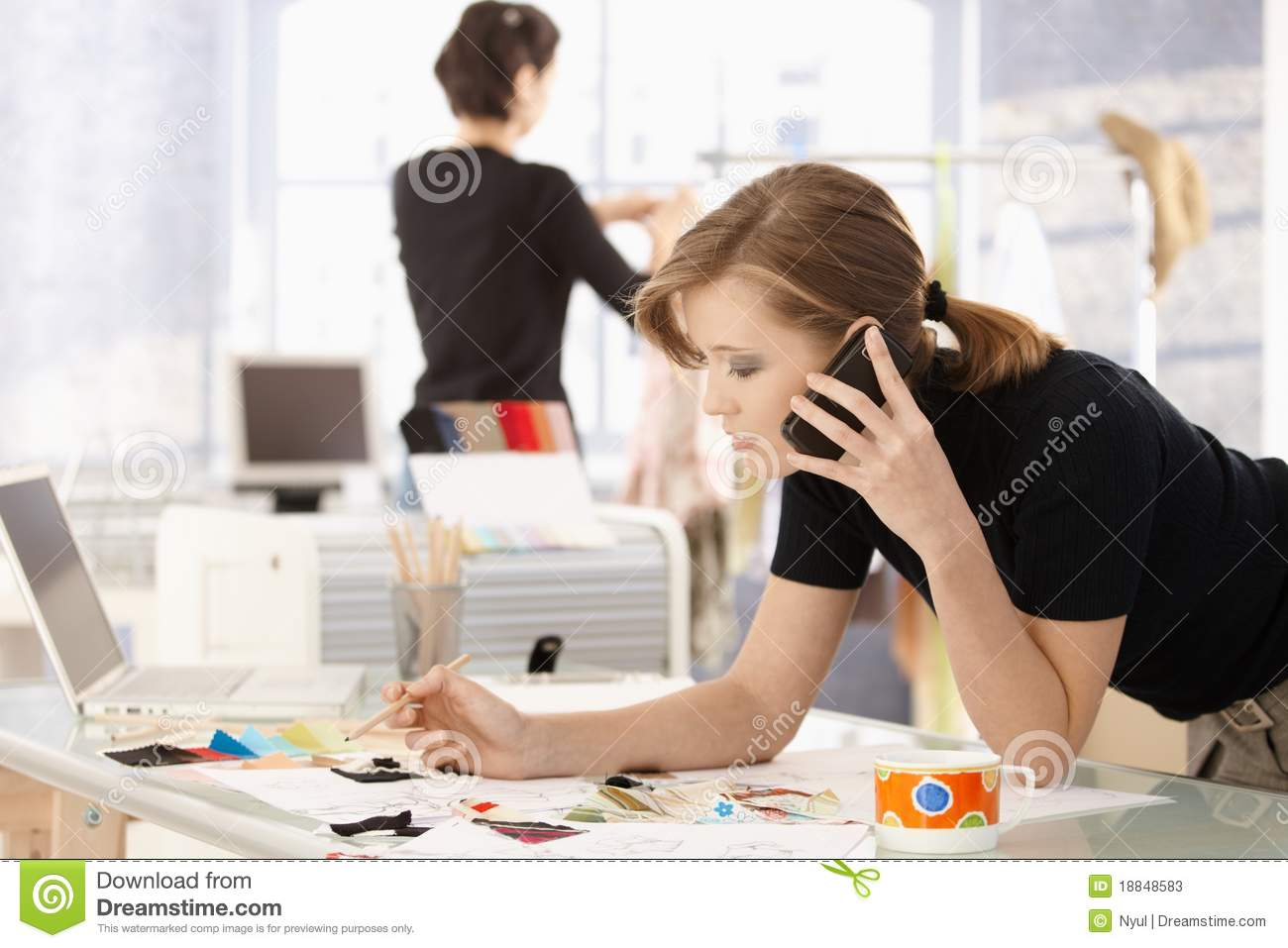 Young attractive female fashion designer leaning on office desk ...