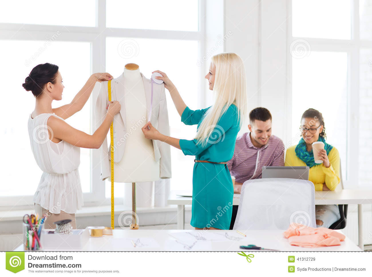 Fashion Designers Measuring Jacket On Mannequin Stock