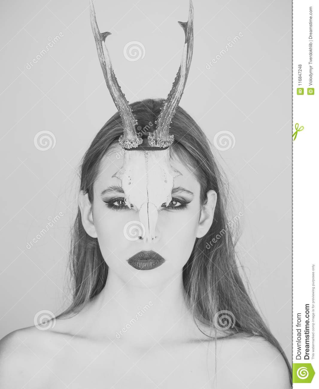 Fashion devil of mystic shaman girl with horns. Woman with makeup and antlers. Beauty look and cosmetics for skincare