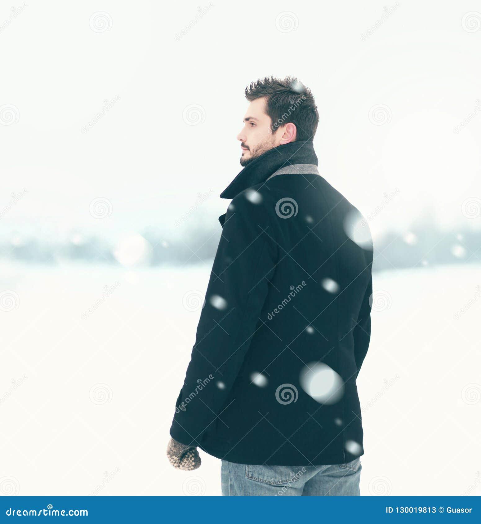 Fashion elegant free man in winter snowstorm looks away
