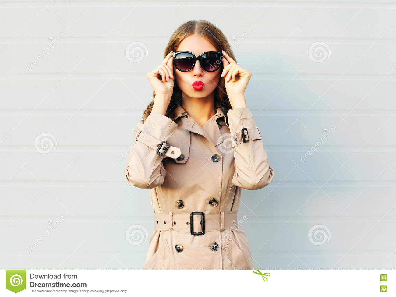 Fashion elegant pretty young woman blowing red lips wearing a black sunglasses coat over grey