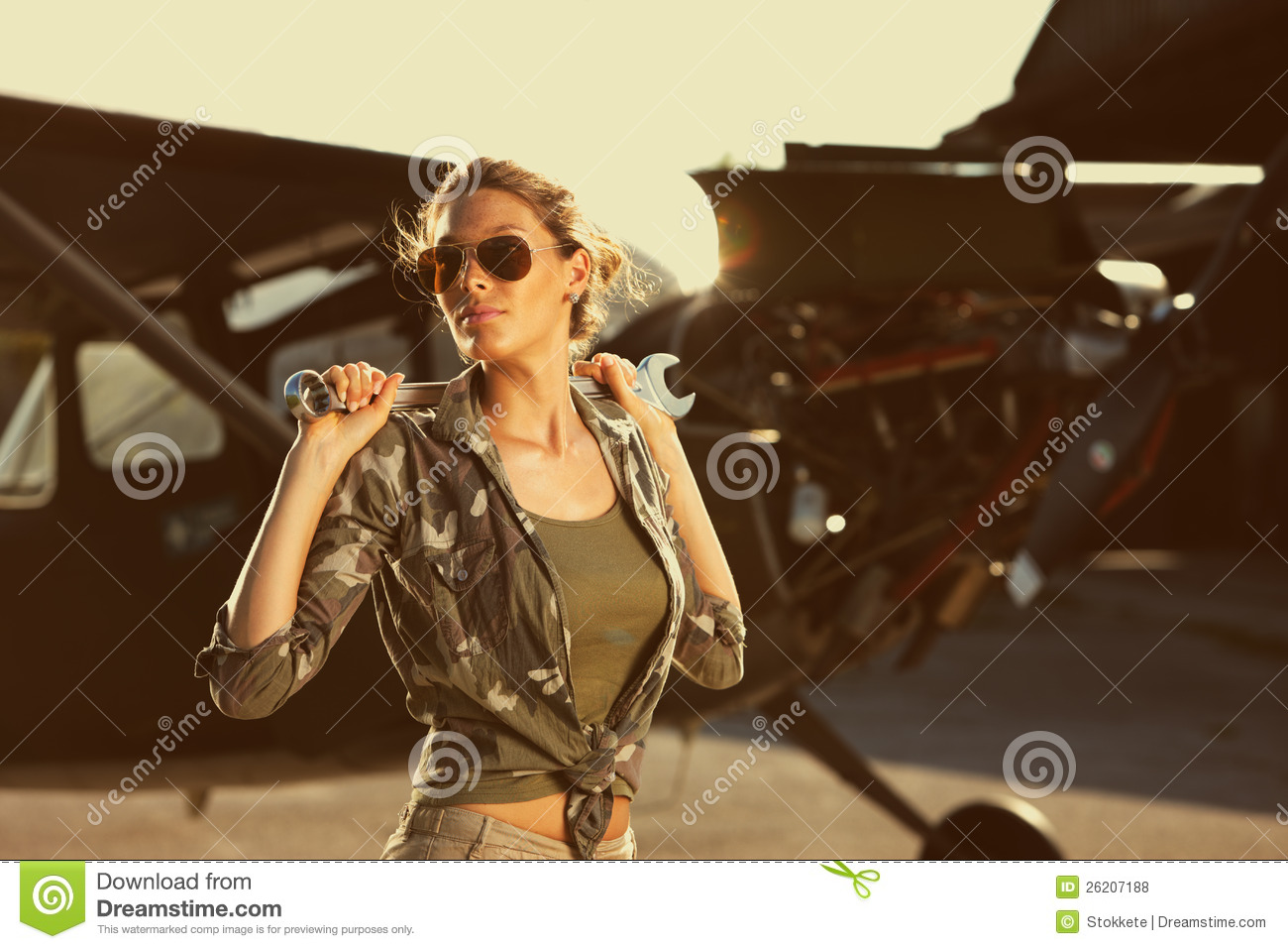 Woman airplane mechanic. Airplane on the background.