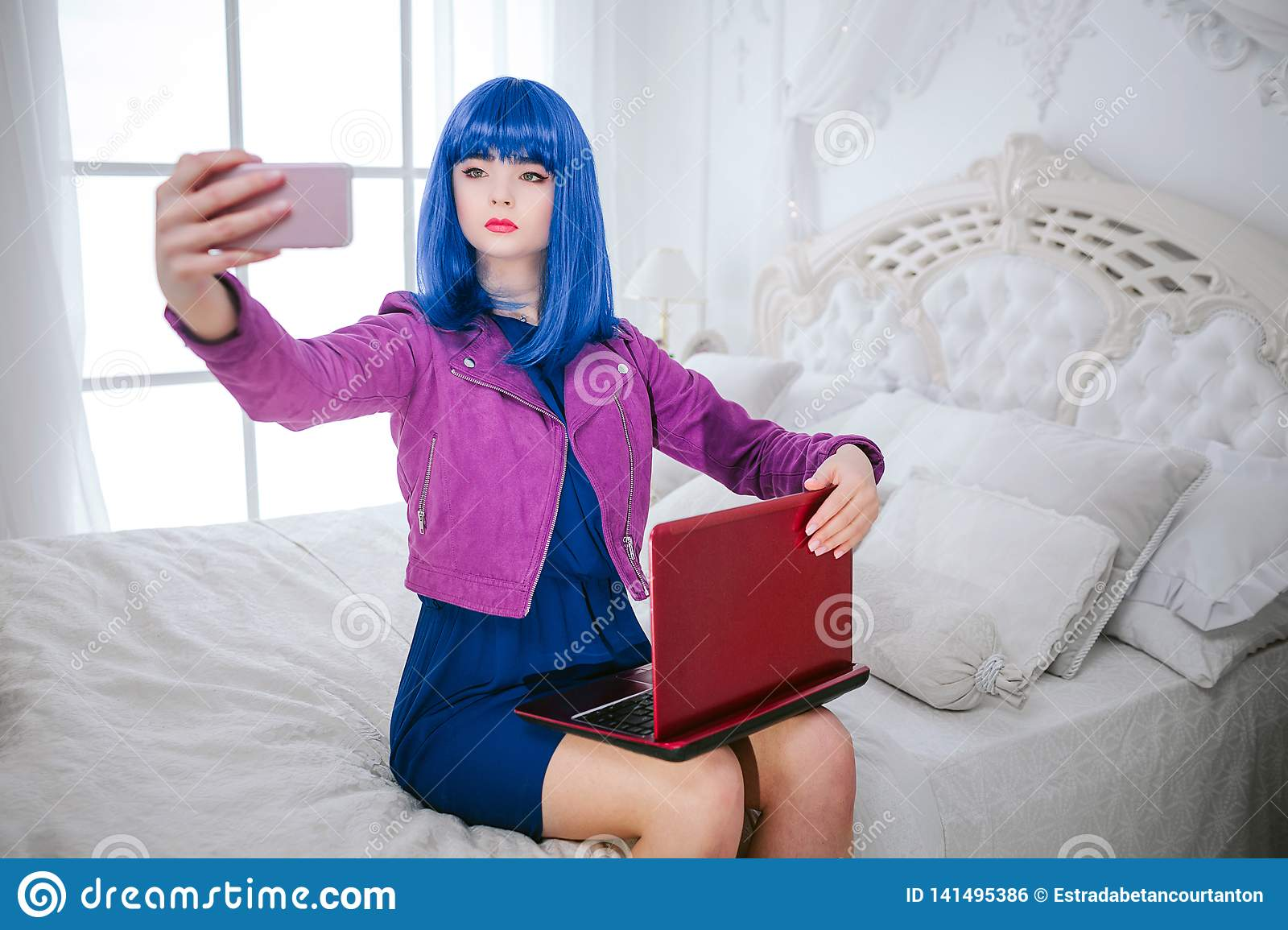 Fashion freak. Glamour emotionless synthetic girl, fake doll with blue hair is holding computer and doing selfie while
